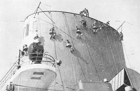 CLEANERS AT WORK on the funnels of one of the great German liners